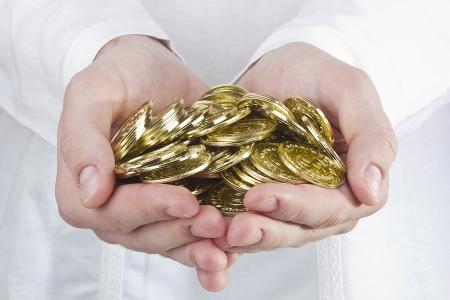 Close-up foto van de handen van de mens houdt gouden munten.
