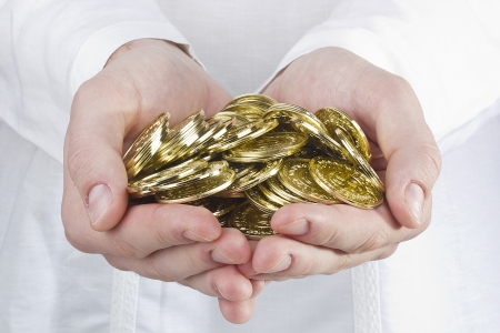 Close-up photograph of mans hands holding golden coins.