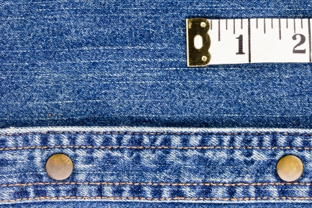 Close-up photograph of measuring tape on denim material. Add your text to the background. Stock Photo - 16244359