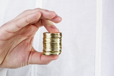 Photographie en gros plan de la main d'un homme tenant une pile de pi�ces de monnaie. Banque d'images