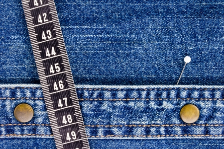 Close-up photograph of measuring tape and a pin on denim material. Stock Photo - 16332935