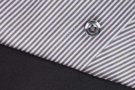 Close-up photograph of a black button on a striped gray pattern.