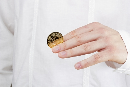 Close-up photograph of a golden coin between a man's fingers. Stock Photo - 16758696