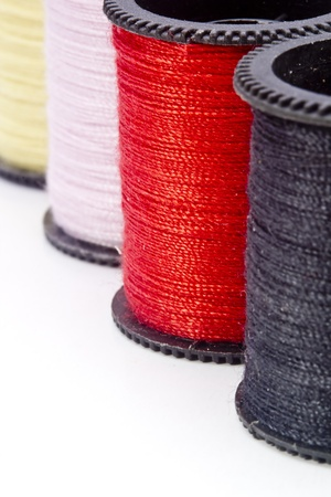 Close-up photograph of red thread next to other spools of thread. photo