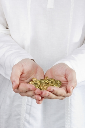 Close-up photograph of mans hands holding golden coins. photo