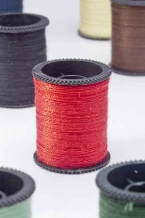 Close-up photograph of a red spool of thread among other spools. photo