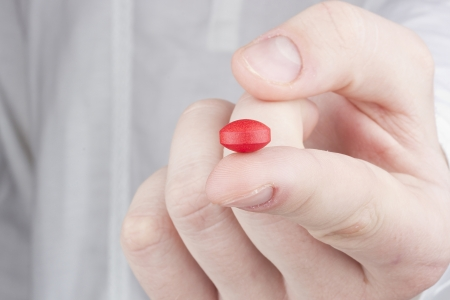 Close-up photograph of a red tablet on a man's finger. photo