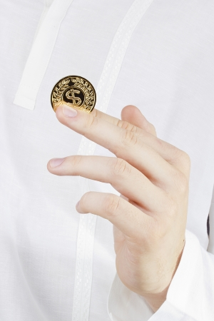 Close-up photograph of a golden coin between a mans fingers. photo