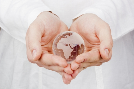 a glass globe in mans hands. photo