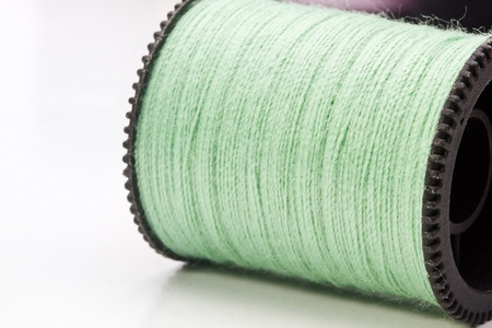 Close-up photograph of a green spool of thread. photo