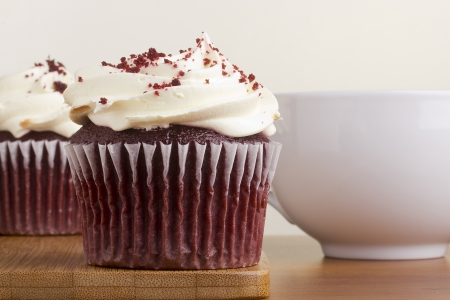 red velvet cupcake: Decorated red velvet cupcake next to a white cup.