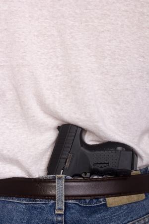 Gun behind his back in his pants. Reklamní fotografie