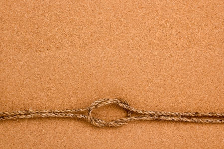 Directly above photograph of an old rope on an orange background.