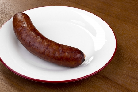 unharmed: Smoked sausage on a white ceramic plate. Stock Photo