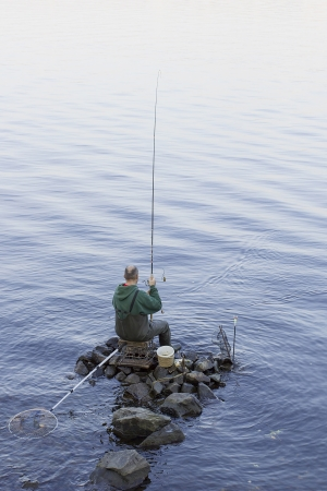 A fisherman with a fishing rod on the rocks.