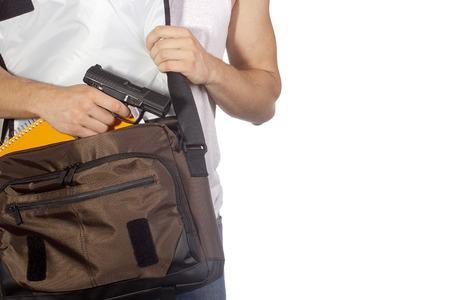Student verbergt pistool in een zak. Misdaad.