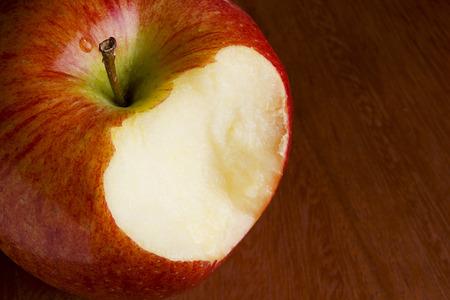 Bitten off apple on a brown wooden surface