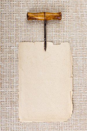 backdrop: Old corkscrew on page parchment placing information. Stock Photo