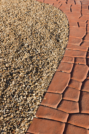Garden path of red stone and decorative gravel. Imagens