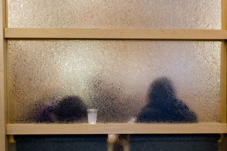 People behind frosted glass office building.