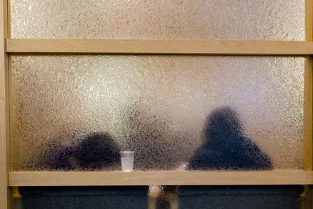 Mensen achter matglas kantoorgebouw. Stockfoto