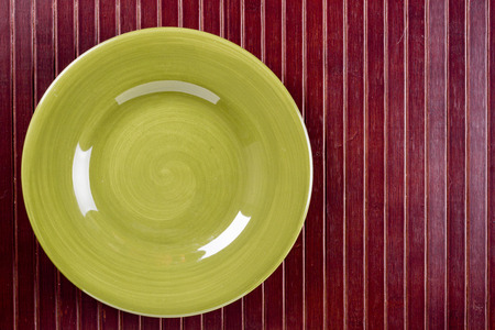dish disk: Ceramic dish on wooden kitchen litter. Cookware. Stock Photo