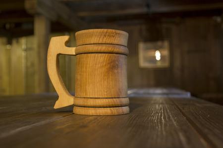 bathe mug: Wooden mug on a table in a tavern. Stock Photo