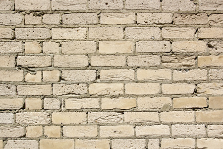Brick wall of a light yellow clay. Industrial background.