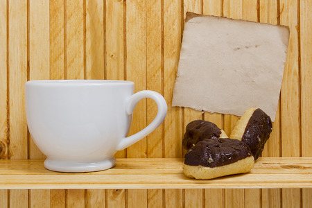 Small eclairs on a shelf next to the cup. photo