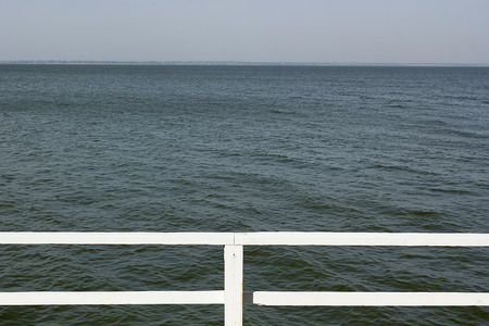 Expanse of water leaving for horizon with wooden railings pier.