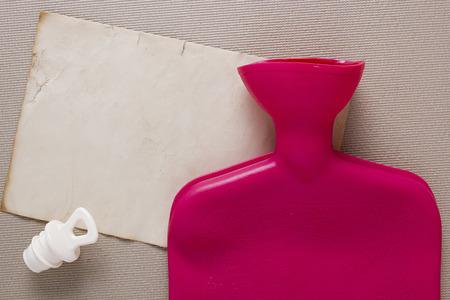 wärmflasche: Medizinische Wärmflasche mit Gummi auf einem grauen Hintergrund.