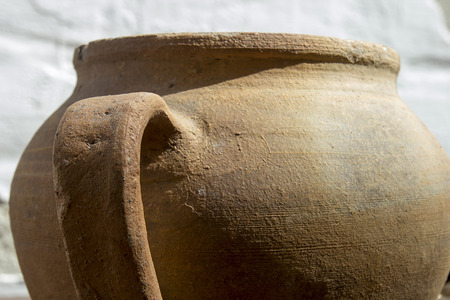 Clay pot with a handle of the old style. Stock Photo