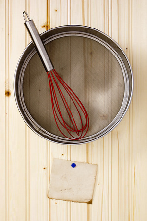 bolter: Sieve on a wooden wall with a paper for information. Stock Photo