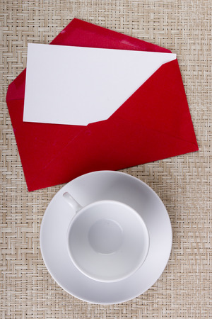 envelope: Red envelope with empty tea cup and saucer.
