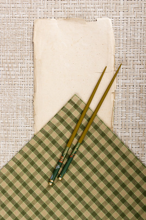 accommodate: Classical chopsticks on a napkin and a piece of paper to accommodate the additional information. Stock Photo