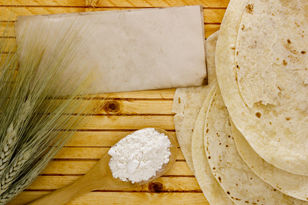 tortillas: Flour in a spoon with wheat ears and tortillas.