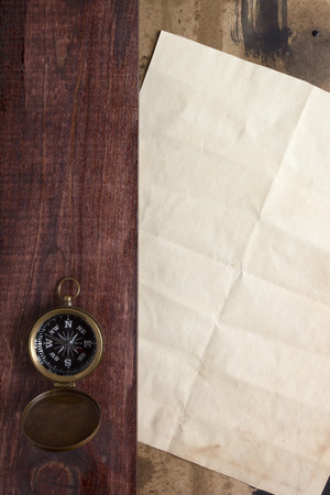 Background traveler with a compass and an old sheet of paper for creativity. photo