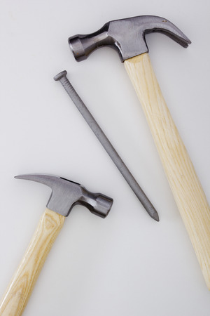pounding head: Two construction hammer and big industrial nail. Stock Photo