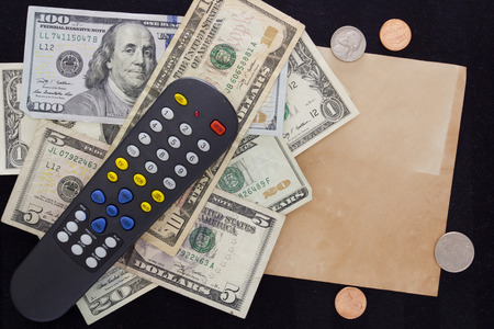 indigence: Utility bills - TV. TV remote switching channels with dollars and cents.