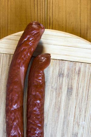hardboard: Smoked sausage on a kitchen cutting board. Stock Photo