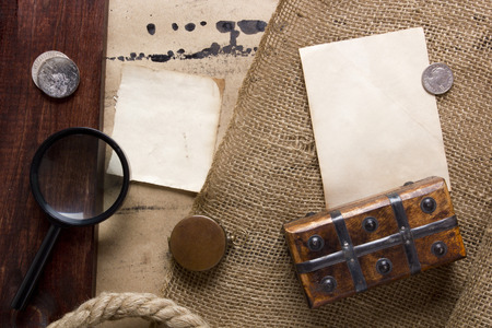 old items: Items related to treasure - coins with a magnifying glass casket on the old background.