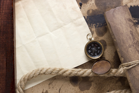 Roll of parchment with a compass and marine rope. photo
