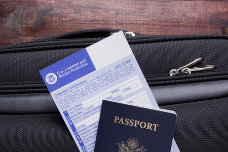 consulate: Customs declaration and passport lie on the road suitcase, passing visa control.