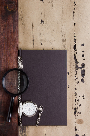 pocketwatch: Book with pocket watch and magnifying glass. Stock Photo