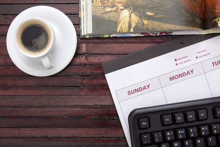 briefing: A cup of coffee on the office calendar.