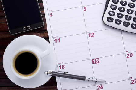 calculator: A cup of coffee on the office calendar.