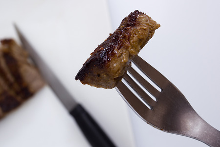 porterhouse: Piece of medium rare steak on a fork. Stock Photo