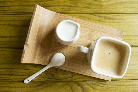 milkman: Coffee set on a special support of a coffee cup, a spoon and a milkman.
