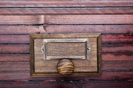 Wooden drawer old-style archive cabinet. On the box set-ply plate. photo