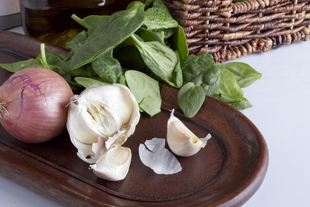 Garlic and onion on a wooden platter, spinach leaves.
